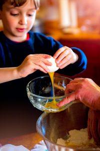 Boy cracking an egg
