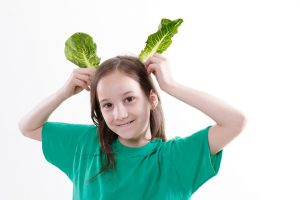 Girl playing with lettuce
